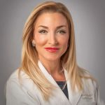 Dr. Stephanie Haridopolos Smiling in Lab Coat